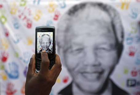 A well-wisher takes a picture using a cell phone of a banner with the image of former South African President Nelson Mandela, outside the Me