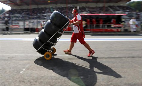 A Ferrari Formula One technician pushes a trolley with Pirelli tyres during the second practice session of the Belgian F1 Grand Prix at the
