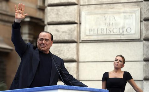 Former Italian Prime Minister Silvio Berlusconi waves to supporters as his girlfriend Francesca Pascale looks on during a rally to protest h