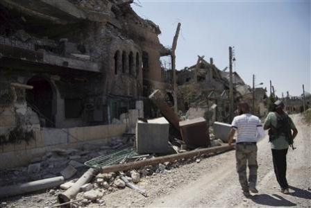 Free Syrian Army fighters walk past damaged buildings and debris in Deir al-Zor August 20, 2013. Picture taken August 20, 2013. REUTERS/Khalil Ashawi
