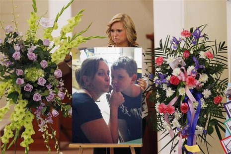 Hannah Anderson positions a photo of her mother Christina Anderson and brother Ethan Anderson on an easel at the memorial service in Guardia
