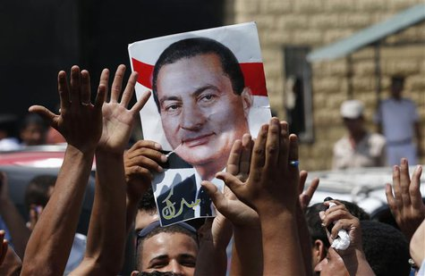 Supporters of former president Hosni Mubarak hold his poster to celebrate his release in front of the main gate of Tora prison, on the outsk