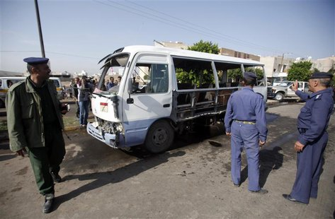 A policeman (L) and air force officers gather at the site of a bomb attack on a military bus in Sanaa August 25, 2013. REUTERS/Khaled Abdull