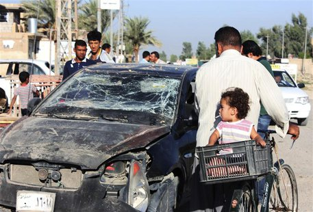 Residents pass by a damaged vehicle a day after a bomb attack in central Baquba, 65 km (40 miles) northeast of Baghdad, August 25, 2013. REU