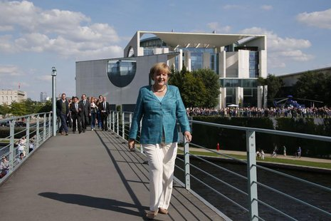 German Chancellor Angela Merkel crosses a footbridge over the river Spree in front of the Chancellery during a German Government 'Open Door