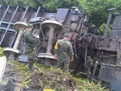 Soldiers stand near the overturned wagons of a derailed train in Huamanguillo, in this August 25, 2013 handout photo provided by Diario Pres