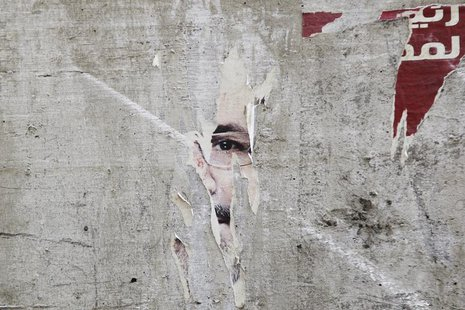 Remnants of a poster of ousted Egyptian President Mohamed Mursi are pictured on a wall on a street in Cairo August 25, 2013. REUTERS/Muhamma