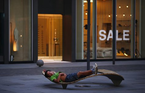 A man sleeps outside a boutique at Taikoo Li Sanlitun North, in Beijing, August 24, 2013. REUTERS/Petar Kujundzic
