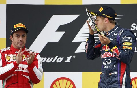 Red Bull Formula One driver Sebastian Vettel of Germany (R) celebrates winning the Belgian F1 Grand Prix beside second-placed Ferrari Formul
