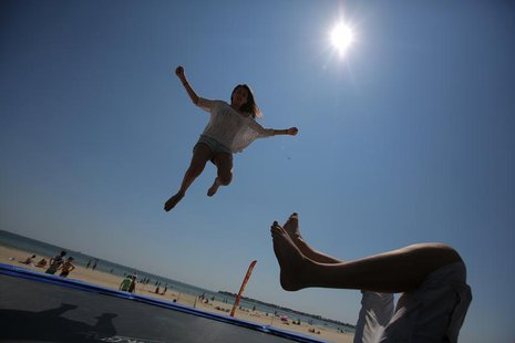Youths play on a trampoline on the beach in La Baule, July 8, 2013 at the start of the summer holidays. REUTERS/Stephane Mahe