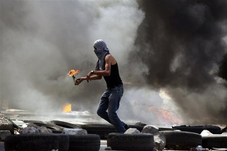A Palestinian protester gets ready to throw a Molotov cocktail during small clashes with Israeli forces following the funerals of Robin Zaye
