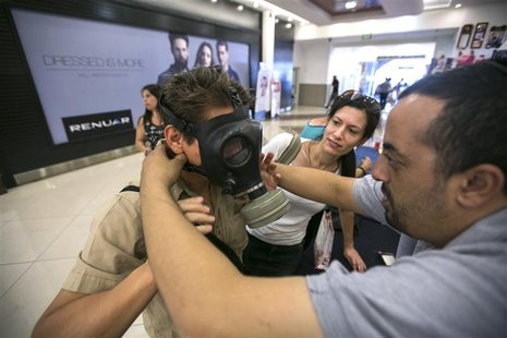 An Israeli Postal Service employee shows a man how to adjust a gas mask at a distribution point at a shopping mall in the West Bank Jewish s
