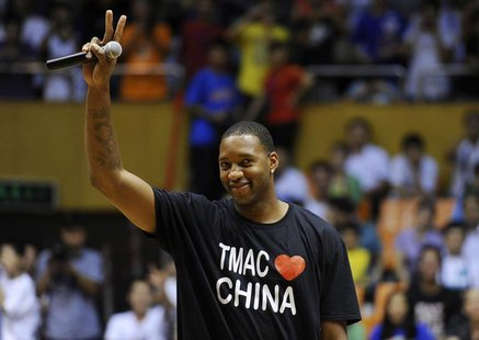 NBA basketball player Tracy McGrady of Detroit Pistons gestures to his fans at a stadium during a promotional event of his China tour in Hef