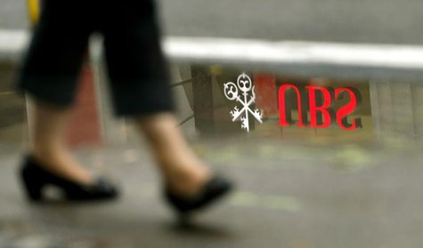 The logo of Swiss bank UBS is reflected in a puddle as a woman walks past, in Zurich July 30, 2013. REUTERS/Arnd Wiegmann