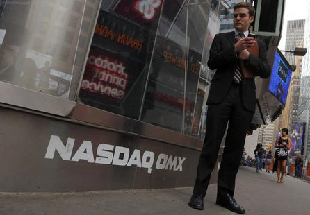 A man stands next to the Nasdaq MarketSite in New York, August 23, 2013. REUTERS/Brendan McDermid