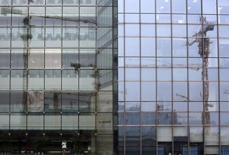 Cranes on a construction site are reflected on a business building in Beijing August 1, 2013. REUTERS/Kim Kyung-Hoon