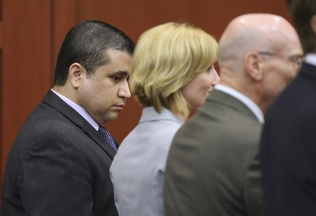George Zimmerman looks down as his defense team Don West (R), and Lorna Truett (C), react upon hearing the verdict in Zimmerman's 2012 shoot