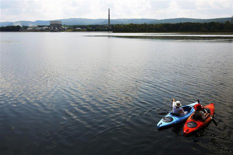 Kayakers paddle in the Connecticut River from Hinsdale, New Hampshire, in front of the Vermont Yankee nuclear power plant in Vernon, Vermont