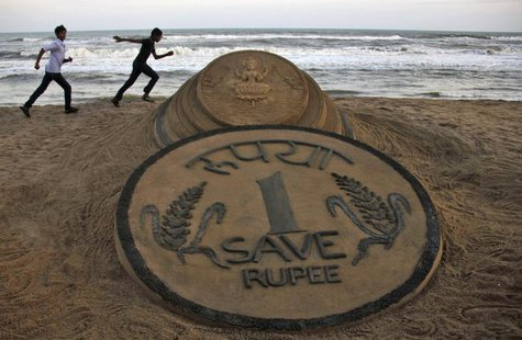 Boys run near a sand sculpture of the Indian Rupee created by Indian sand artist Sudarshan Pattnaik at golden sea beach at Puri in the easte