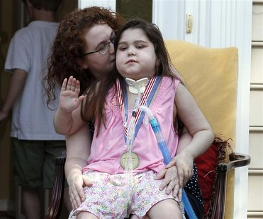 Sarah Murnaghan (R), an 11-year-old girl who underwent a double lung transplant, sits on her mother Janet's lap outside their home in Newtow