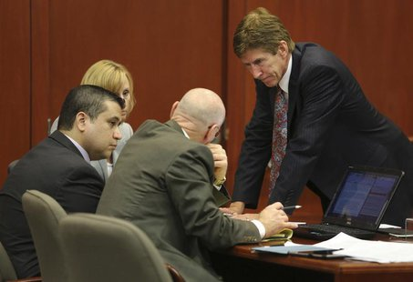 George Zimmerman confers with his defense counsel, Mark O'Mara (R), Don West (2nd R), and Lorna Truett (background) after working out the wo