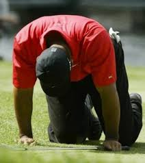 Tiger Woods on his knees after his second shot on the 13th hole of The Barclays.