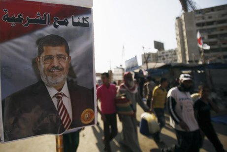 A poster of deposed Egyptian President Mohamed Mursi is seen as members of the Muslim Brotherhood and supporters of Mursi walk at Rabaa Adaw