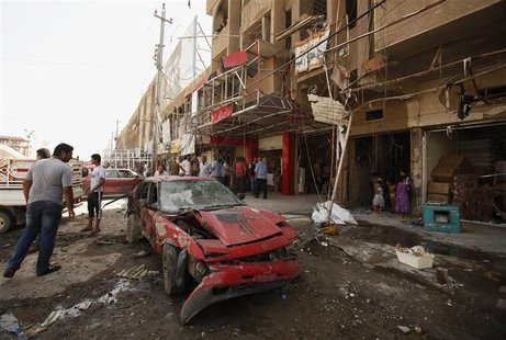 A man looks at a damaged vehicle after a car bomb attack in Baghdad's al-Shaab district August 28, 2013. REUTERS/Saad Shalash