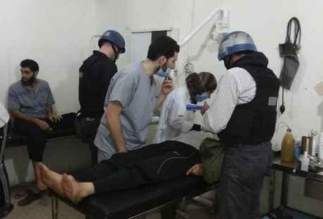 U.N. chemical weapons experts visit people affected by an apparent gas attack, at a hospital in the southwestern Damascus suburb of Mouadami
