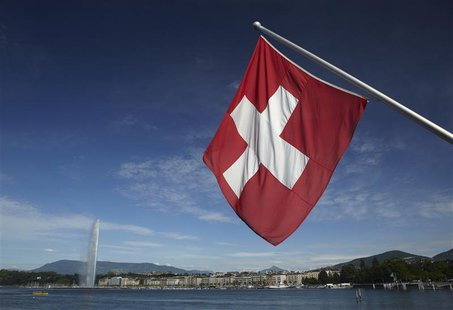 A Swiss flag is pictured next to the Jet d'Eau (water fountain), and the Lake Leman from the St-Pierre Cathedrale in Geneva June 5, 2012. RE