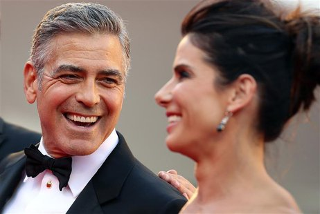 "U.S. actor George Clooney (L) smiles next to actress Sandra Bullock as their arrive for the premiere of ""Gravity"" at the 70th Venice Film Fe"