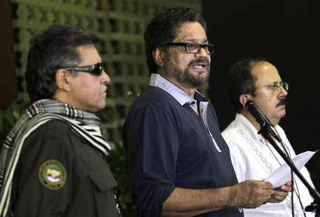 Colombia's Revolutionary Armed Forces of Colombia (FARC) lead negotiator Ivan Marquez (C) reads a document as (FARC) members Jesus Santrich