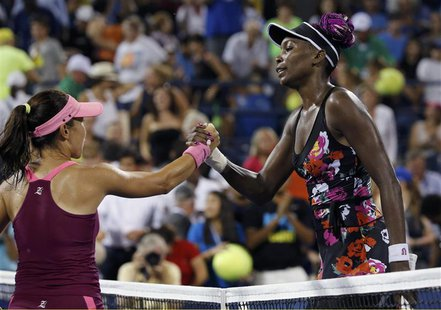Jie Zheng of China (L) shakes hands wirh Venus Williams of the U.S. after Zheng won their second round match at the U.S. Open tennis champio