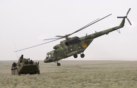 An MI-17 helicopter flies by an armoured personnel carrier (APC) during the Steppe Eagle 2010 joint tactical military exercise at Ili milita