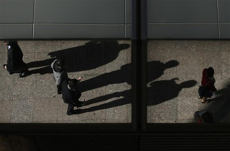 Office workers are reflected on a building as they cast their shadows during lunch time in central Sydney July 30, 2013. REUTERS/Daniel Muno