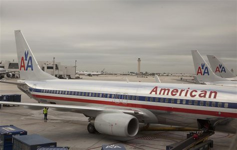A worker walks underneath an American Airlines airplane at Miami International airport in Miami, Florida November 29, 2011. REUTERS/Lucas Ja