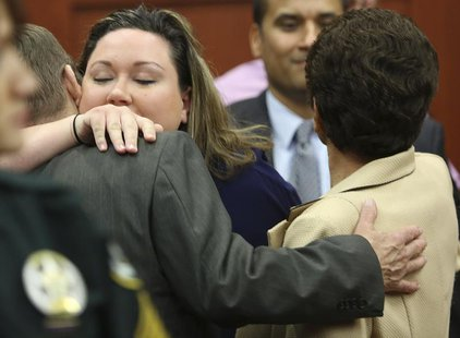 George Zimmerman's wife, Shellie (2nd L), hugs her Father-in-law Robert Zimmerman Sr. (L) and after her husband was found not guilty in the