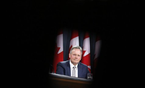 Bank of Canada Governor Stephen Poloz is framed by seats while taking part in a news conference upon the release of the Monetary Policy Repo