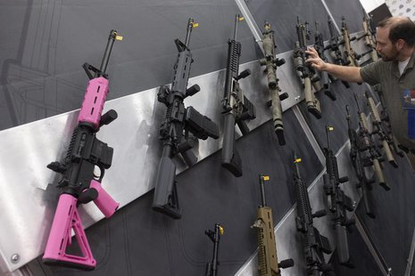 A pink assault rifle hangs among others at an exhibit booth at the George R. Brown convention center, the site for the National Rifle Associ
