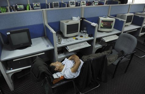 An investor sleeps on chairs next to a computer screen showing stock information at a brokerage house in Hefei, Anhui province June 13, 2013