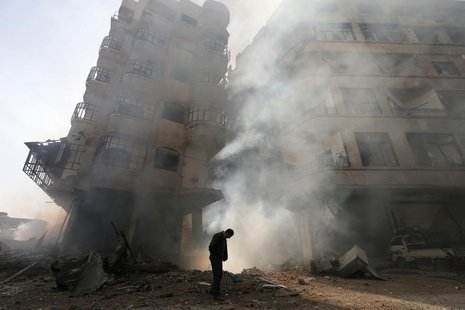 A man walks in front of a burning building after a Syrian Air force air strike in Ain Tarma neighbourhood of Damascus in this January 27, 20