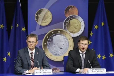 Latvia's Prime Minister Valdis Dombrovskis and Finance Minister Andris Vilks (L) address a news conference on the adoption of the euro by La