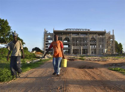 Workers walk in front of the construction site of the new building that will house the administrative headquarters for the Kenya Ports Autho