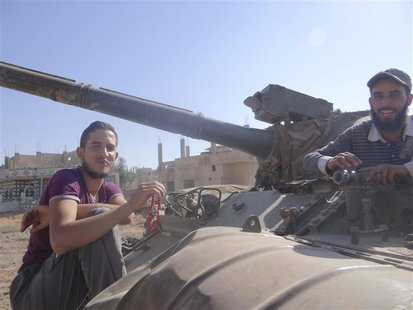 Free Syrian Army (FSA) fighters are seen at a tank that belonged to forces loyal to Syria's President Bashar al-Assad after the FSA said the
