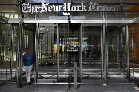 A woman exits the New York Times Building in New York August 14, 2013. REUTERS/Brendan McDermid
