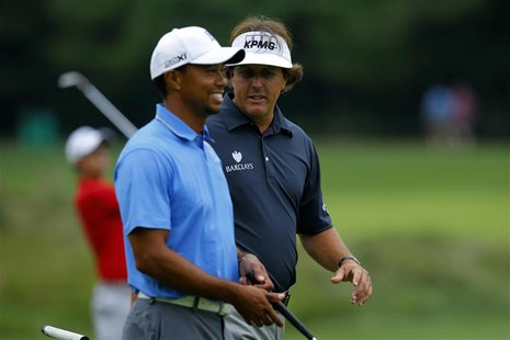 Tiger Woods (L) and Phil Mickelson, both of the United States, walk up the sixth fairway during the first round of the Deutsche Bank Champio