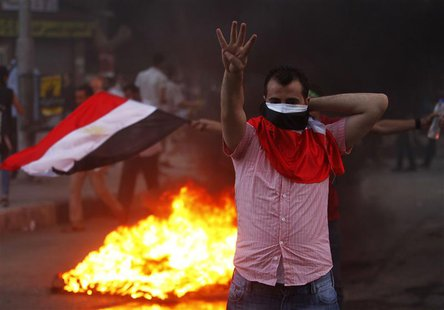 "A supporter of ousted Egyptian President Mohamed Mursi makes the ""Rabaa"" or ""Four"" gesture during clashes at Mohandiseen in Cairo August 30,"