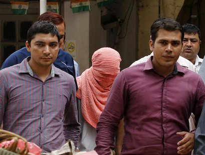 Plainclothes policemen escort an Indian teenager (head covered with towel) after he was sentenced at a juvenile court in New Delhi August 31