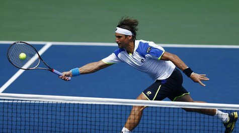 David Ferrer of Spain lunges to make a shot at the net against Mikhail Kukushkin of Kazakhstan at the U.S. Open tennis championships in New