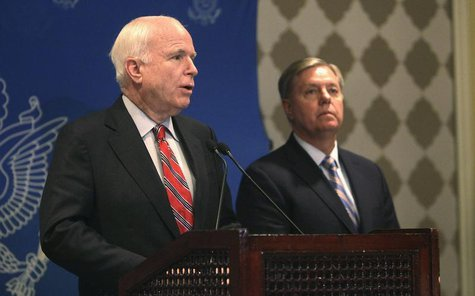U.S. Senator John McCain speaks as compatriot Senator Lindsey Graham (R) looks on during a news conference in Cairo, August 6, 2013. REUTERS